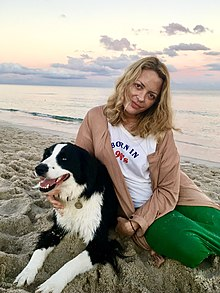 Wurtzel seated in sand next to a dog