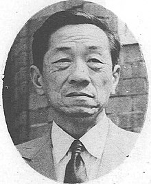 Asian man facing front, in suit and tie.