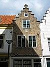 foto van Huis met gepleisterde trapgevel. De treden afgedekt met natuurstenen platen. Moderne winkelpui