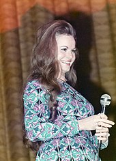A young woman with long brown hair wearing a dress with an intricate multi-coloured pattern and holding a microphone