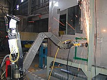 A robot with a metal arm is using its grinding wheel to cut into a wall, sending a shower of sparks upward.