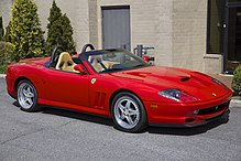 A sporty red two-seat convertible facing right at a mild three-quarter orientation to the viewer, parked in front of a light brown wall