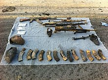 Various weapons, including assault rifles and ammunition canisters, laid out on a blanket on the ground