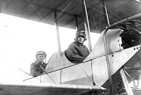 Two men in flying gear seated in tandem open cockpits of a biplane