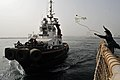 A Sailor heaves a mooring line to a tugboat. (6846520023).jpg