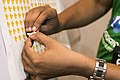 A Wikimedian peeling off a sticker during Odia Wikipedia 16.jpg