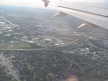 Aerial view of a cloverleaf interchange in a densely popoulated region; an airplane wing is visible at the top of the image.
