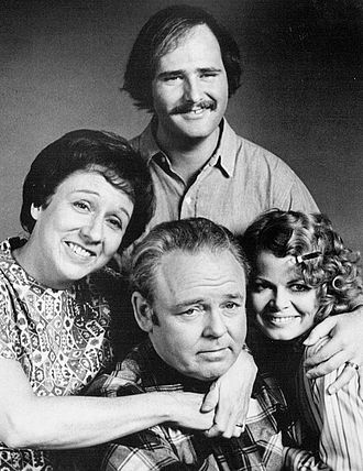"Edith Bunker - Edith Bunker (Jean Stapleton, left) with her husband Archie (Carroll O'Connor, bottom). her daughter Gloria (Sally Struthers, right) and her son in law Mike ""Meathead"" Stivic (Rob Reiner, top) in cast photo"