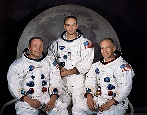 Three astronauts in spacesuits without helmets sitting in front of a large photo of the Moon.