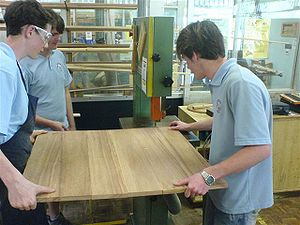 Bandsaw - Students maneuver a large laminated board through a bandsaw together