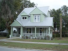 a green two story house with shingles