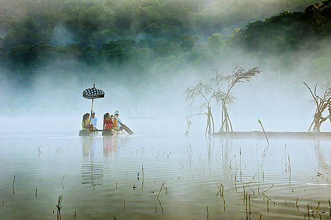 Peoples in Lake Tamblingan, Bali use traditional boats to cross. They left early in the morning to pray at the temple