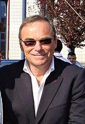 Photographie d'un homme vêtu d'une chemise blanche, d'une veste noire et porteur de lunettes de soleil