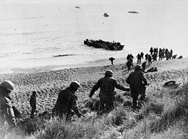 Men running down cliff towards a waiting boat on the shore line