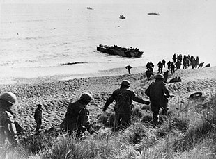 Men running down a cliff towards a waiting boat on the shore line