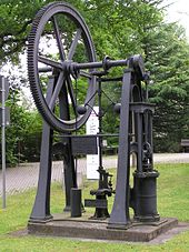 Black painted metal machine that stands in an outdoor exhibition area.  A gear wheel with a diameter of more than one meter is connected to a pressure cylinder (about 40 cm high and 20 cm wide) via a crankshaft.  A speed limiter is connected via small gears.  The machine has no housing and is about 2 meters high.