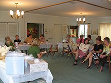 women sitting in chairs at a party with a few gifts stacked on a table a bridal shower traditionally