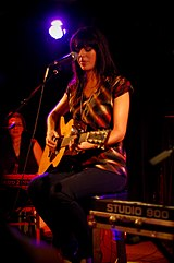 A woman with long black hair wearing a red and black striped singlet. She is seated and playing a guitar in front of a microphone.