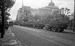 Trucks travelling along wide tree-lined street with large old building in the background