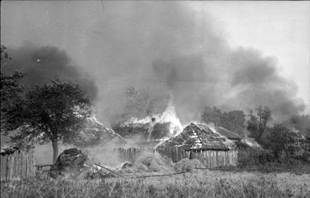 "Nazi Germany's scorched-earth policy in the Soviet Union, 1943. Photograph taken by a Wehrmacht propaganda company; original 1943 caption reads: ""Russia. Burning houses / huts in village"". Bundesarchiv Bild 101I-087-3693-07A, Russland, brennende Ortschaft.jpg"