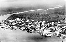 Black and white photo of an industrial installation located next to a body of water. It includes a large number of white storage tanks and buildings, as well as a wharf. A large ship is docked at the wharf.