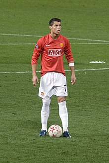 Cristiano Ronaldo – wearing a long-sleeved red jersey, white shorts with a number 7 on the left-leg side and a white armband on the left arm – prepares to take a free kick.