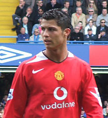 Head and torso of a man wearing a red long-sleeved football shirt. He is in front of a crowded stand of fans.