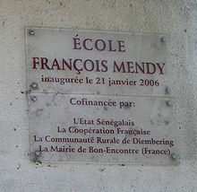 "A clear plaque on a grey wall stating ""École François Mendy"" at the top with smaller writing below"