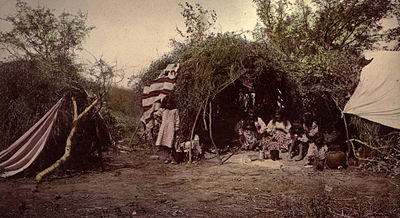 Chiricahua medicine man and family in wickiup