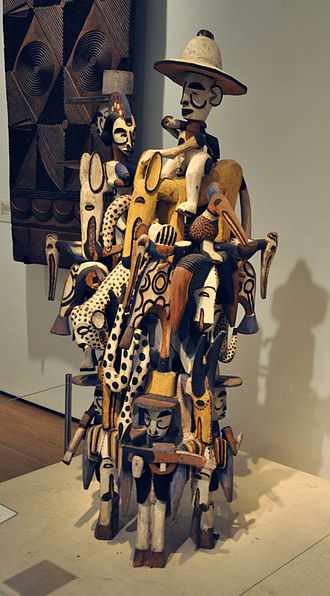 Igbo culture - Complex wooden carving depicting images of power and daily life, such as horsemen, imported goods, military insignia, Europeans, rifles, wild beasts and masqueraders.