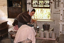 Young woman in period clothing at a pottery wheel