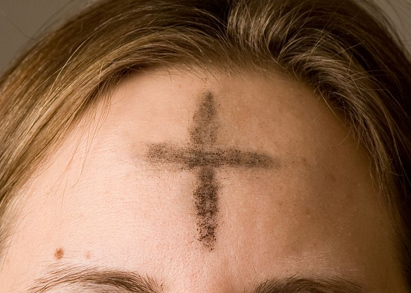 Cross of ashes on a girl's forehead