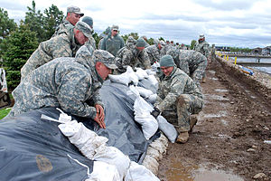 Defense.gov News Photo 110531-A-3986W-138 - U.S. Army Sgt. Aaron Pallansch right uses sandbags to secure a plastic tarp to the top of a dike at Mandan s Waste Water Treatment Plant in Mandan.jpg