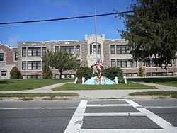 The Eastport Elementary School on Montauk Highway with a World War I memorial in front of it.