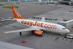 Avión de easyJet en el Aeropuerto de Schiphol, Amsterdam, Países Bajos. Observe los vehículos presentes en torno a la aeronave.