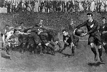 Painting of the aftermath of a rugby scrum, with a player from one team running with the ball towards the opposition goal-line while an opponent runs to intercept him.
