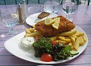 A plate of fish and chips, with salad, dip, lemon slices and a glass of water.