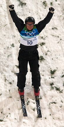 A man skis down a snow-covered slope with his arms in the air and fists closed. He is wearing black equipment with a blue-and-white vest bearing the Olympic rings and the number ten; a black helmet, black-and-white gloves, protective glasses, and red boots attached to black skis.
