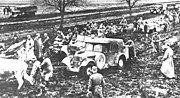 a black and white photograph of troops and animals pulling vehicles out of the mud