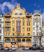 La façade sur rue d'un bâtiment art nouveau, à dominante jaune, à cinq étages.