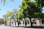 Grosvenor House is situated next to the Dutch Reformed Church in Drostdy Street. Grosvenor House is associated with the oldest and best-known Stellenbosch and, therefore, South African families. The land on which it stands was granted to Christiaan Ludolph Neethling in 1781. He came to the Cape from Germany in 1741 and became the progenitor of this widespread Afrikaans family. The building also provides a clear demonstration of how a simple structure could develop into a worthy example of Cape architecture. The house that Christiaan Neethling built consisted of a row of single-storeyed thatched rooms in Drostdy Street. At the end of the 18th and beginning of the 19th centuries a gable was added above the front door and a room was built on at the back which gave the building the shape of a T. Later additions made it into a full-scale H-shaped house. The sick-comforter, Herold, F added a second storey with a flat roof, an alteration that was at first probably confined to the front part of the house. These changes gave the house a completely new façade: four fluted pilasters with a richly ornamented cornice; a teak stable-door framed by shorter, ribbed pilasters; teak sash-windows with inner shutters of stinkwood and, right at the top, a little palm tree in bas relief, taken from the crest of the community. This is how the house still stands today. The outbuildings on either side of the main house were probably also built in Herold time. Frederick Neethling who occupied the house just when the late Georgian style was fashionable, was probably responsible for the wagon-wheel fanlight. The house, a cultural treasure in its own right, is a worthy repository for relics of the history of Stellenbosch and its neighbourhood.