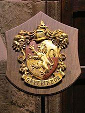 Blason représentant un lion doré et dressé, sur fond de rouge et d'or. Sous le blason est inscrit « Gryffondor » en anglais. Sur la partie supérieure du blason est dessiné un heaume