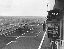 The deck of an aircraft carrier with a propeller aircraft towards the front of the ship. Some of the ship's superstructure is at right, including a board displaying the wind conditions