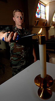 A United States Air Force chaplain's assistant lights an altar candle with a long-handled lighter in preparation for a Christian worship service.