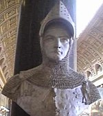 A bust in monochrome grey of a man wearing late-Medieval armour