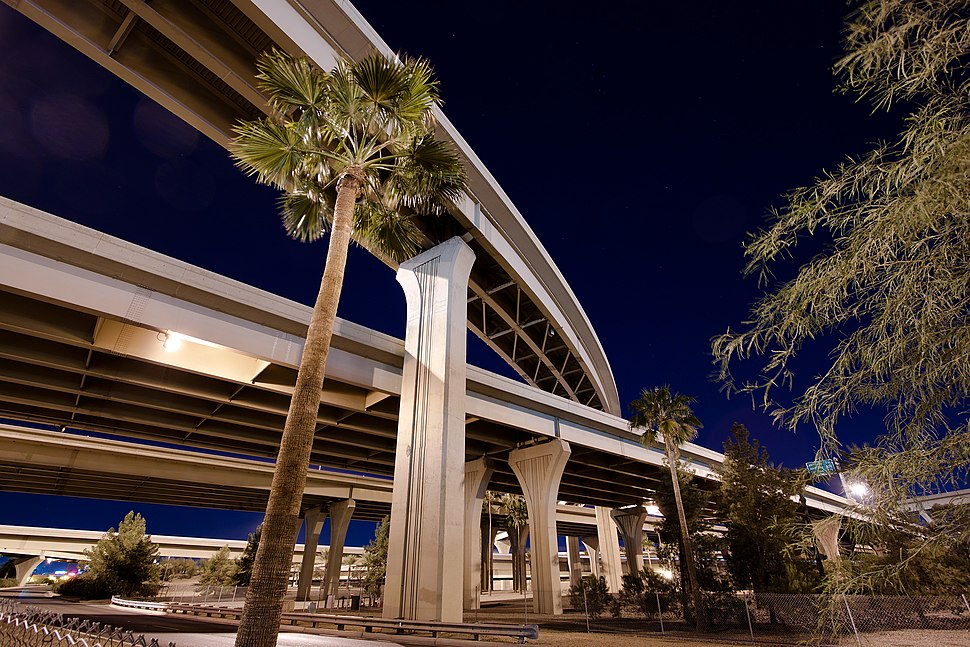 """photo showing the multiple levels of roadways at the interchange between Interstates ten and seventeen, called """"the stack"""" in downtown Phoenix at night."""