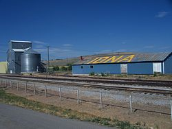 A grain elevator near the train tracks.