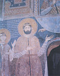 Medieval mural portrait on the interior walls of a church depicting a tall bearded man in a noble's attire