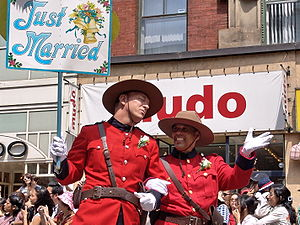 Pride Toronto - Two men dressed in faux Royal Canadian Mounted Police costumes celebrate their wedding.