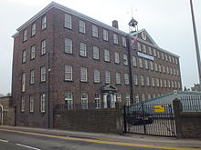 A four storey brick building, on the long side to the right there are 17 windows on each floor, on the short side there are only 3 window each floor. Over the central five windows is a triangular pediment surmounted by a cupola with a bell. Over the ground floor door, four bays from the near corner is the date 1790.
